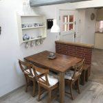Haustüre von innen, Essbereich mit Holztisch, drei Stühlen und Bank.