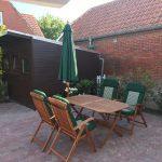 Sonnenschirm geschlossen, Gartentisch mit Stühlen in Holz.