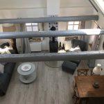 Galerieblick, Wohnzimmer mit Kaminofen, Essbereich, Ohrensessel, Holzboden, Couch, Querbalken