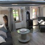 Graue Couch, Holzfußboden, Beistelltisch, Kaminofen, Ohrensessel, heller Raum