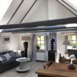 Essbereich, Couch, Beistelltisch, freie Balken, heller Raum, Blick in den Dachgiebel. Kaminofen.